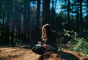 Girl writing in woods